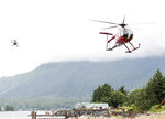 Two helicopters carrying survivors from a plane crash approach Ketchikan, Alaska, Tuesday, July 10, 2018, after the crash of a Taquan Air float plane on Prince of Wales Island's Mt. Jumbo. The chartered Taquan Air flight plane crashed Tuesday on a rocky mountainside near Ketchikan. Everyone survived and were rescued hours later by the U.S. Coast Guard. (Dustin Safranek/The Ketchikan Daily News via AP)