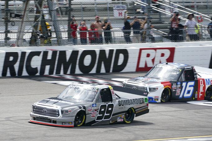Ben Rhodes (99) leads Austin Hill (16) past the start finish line at the start of the NASCAR Truck Series auto race at Richmond International Raceway in Richmond, Va., Saturday, April 17, 2021. (AP Photo/Steve Helber)