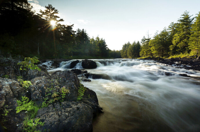 FILE - In this Aug. 9, 2017 file photo, the East Branch of the Penobscot River flows over Pond Pitch in the Katahdin Woods and Waters National Monument, in northern Maine. The Friends of Katahdin Woods and Waters group says it's pleased with progress in the three years since the national monument was created by President Barack Obama. The group was hosting a celebration Saturday, Aug. 24, 2019, night to mark the third anniversary of the monument with music, dinner, awards and an auction. (AP Photo/Robert F. Bukaty)