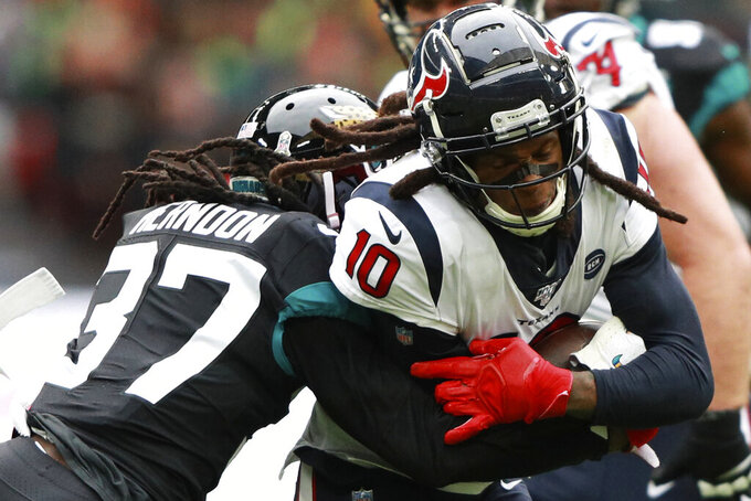 Houston Texans wide receiver DeAndre Hopkins (10) runs into Jacksonville Jaguars cornerback Tre Herndon (37) during the first half of an NFL football game at Wembley Stadium, Sunday, Nov. 3, 2019, in London. (AP Photo/Ian Walton)
