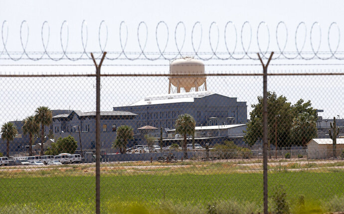 FILE -This July 23, 2014, file photo, shows a state prison in Florence, Ariz. The state of Arizona has agreed to pay $100,000 to settle a lawsuit by a former corrections officer who alleged his co-workers and supervisors repeatedly harassed him over his status as a transgender man. The officer, who filed the lawsuit under a pseudonym due to safety and privacy concerns, resigned in 2016 after working nearly 11 years in state prisons in Florence and Douglas. (AP Photo/File)