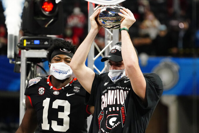 Georgia place kicker Jack Podlesny (96) and offensive player of the game, holds the championship tropy after the Peach Bowl NCAA college football game against Cincinnati, Friday, Jan. 1, 2021, in Atlanta. Georgia won 22-21. (AP Photo/Brynn Anderson)