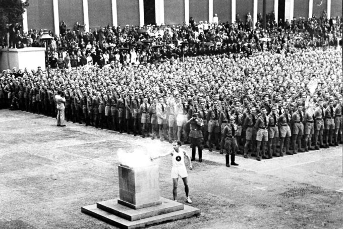 The Olympic torch in Lustgarten, Berlin, is lit Aug. 1, 1936, where will be guarded by members of the Hitler Youth until it is brought to the Olympic stadium for the opening of the games in the afternoon. The torch relay was not always a fixture of the modern Olympics, which began in 1896. The relay tradition began with Adolph Hitler's 1936 Olympics in Berlin. (AP Photo)
