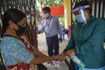 A Nepalese health worker sanitizes the hands of a woman as she arrives gets inoculated against the coronavirus in Kathmandu, Nepal, Tuesday, June 8, 2021. Nepal resumed its stalled coronavirus vaccination campaign on Tuesday with 1 million doses given by China after the Himalayan nation made international pleas for help with a shortage of doses. (AP Photos/Bikram Rai)