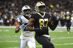 New Orleans Saints tight end Jared Cook (87) scores a touchdown ahead of Carolina Panthers strong safety Eric Reid (25), during the second half at an NFL football game, Sunday, Nov. 24, 2019, in New Orleans. (AP Photo/Bill Feig)