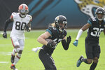 Jacksonville Jaguars safety Andrew Wingard, center, runs after recovering a Cleveland Browns fumble as wide receiver Jarvis Landry (80) gives chase during the first half of an NFL football game, Sunday, Nov. 29, 2020, in Jacksonville, Fla. (AP Photo/Phelan M. Ebenhack)