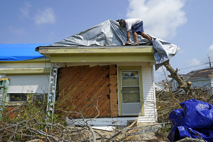 Gary Johnston works to put a tarp on the roof his mother-in-laws damaged home in the aftermath of Hurricane Ida, Thursday, Sept. 2, 2021, in Golden Meadow, La. (AP Photo/David J. Phillip)