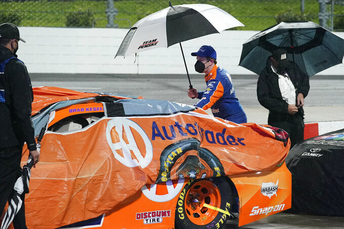 Brad Keselowski, center, helps to cover his car during a rain delay in the NASCAR Cup Series auto race at Martinsville Speedway in Martinsville, Va., Saturday, April 10, 2021. (AP Photo/Steve Helber)