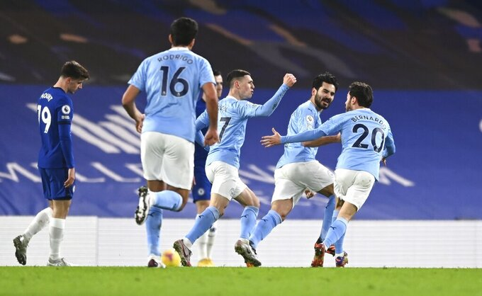 Manchester City's Ilkay Gundogan, second right, celebrates after scoring the opening goal with Manchester City's Bernardo Silva, right, and Manchester City' Phil Foden, centre, during the English Premier League soccer match between Chelsea and Manchester City at Stamford Bridge, London, England, Sunday, Jan. 3, 2021. (Shaun Botterill/Pool via AP)