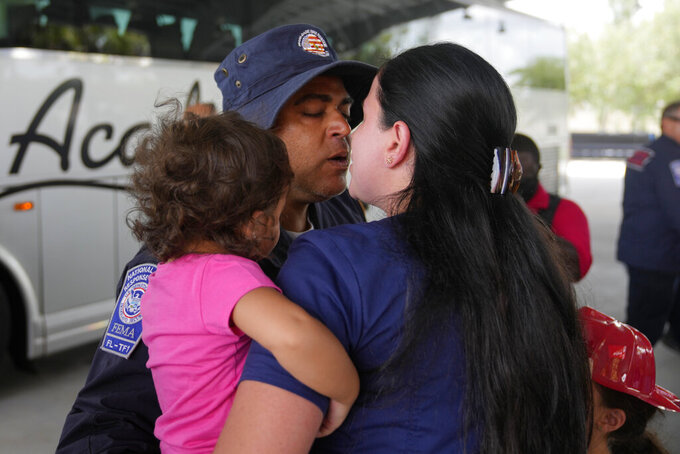 A rescue worker greets his loved ones as members of Miami-Dade Fire Rescue's urban search and rescue team are reunited with their families after weeks of working on the rubble pile at the collapsed Champlain Towers South condominium, on Friday, July 23, 2021, in Doral, Fla. (AP Photo/Rebecca Blackwell)