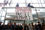 Activists block a shopping center, in the business district of Paris, La Défense, in Paris, Friday, Nov. 29, 2019. People don't celebrate Thanksgiving in France, or Denmark, or the Czech Republic, but they do shop on Black Friday. The U.S. sales phenomenon has spread to retailers across the Atlantic in recent years. The banner reads «Let's burn capitalism, not oil».(AP Photo/Thibault Camus)