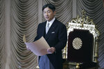 Japan's Emperor Naruhito reads a statement to open formally an extraordinary session at the upper house of parliament in Tokyo Friday, Oct. 4, 2019. (AP Photo/Eugene Hoshiko)