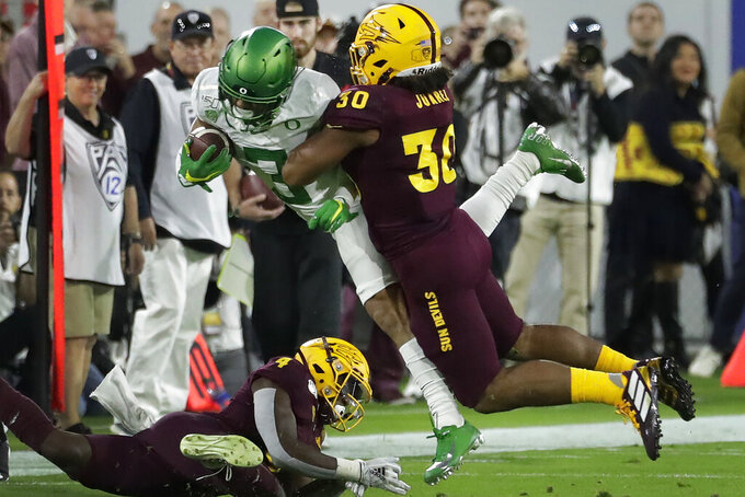 Oregon wide receiver Johnny Johnson III (3) is hit by Arizona State linebacker Elijah Juarez (30) during the first half of an NCAA college football game Saturday, Nov. 23, 2019, in Tempe, Ariz. (AP Photo/Matt York)
