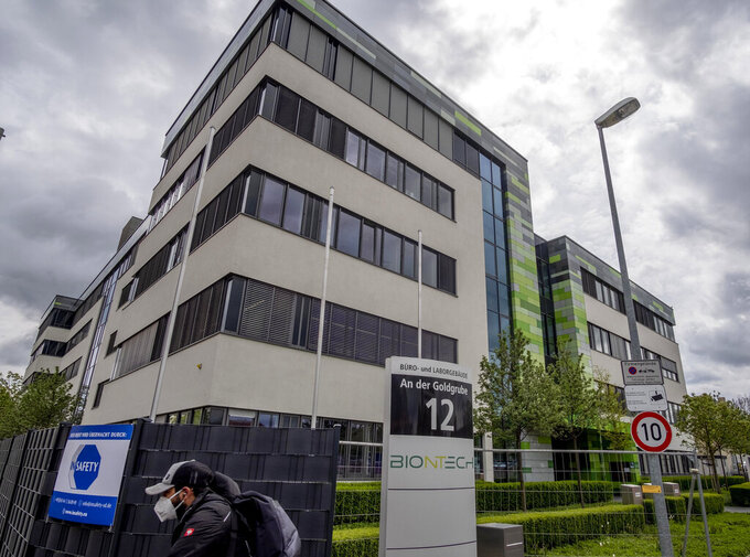 """FILE - In this May 6, 2021 file photo a man with a face mask leaves the headquarters of the German biotechnology company """"BioNTech"""" in Mainz, Germany. (AP Photo/Michael Probst, file)"""