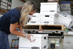 Sarah Edwards, President of Yes on 805, disinfects boxes of petitions as the group delivers 260,000 gathered signatures to the Secretary of State's office Monday, June 1, 2020, in Oklahoma City, to put sentencing reform on a 2020 ballot. (AP Photo/Sue Ogrocki, Pool)