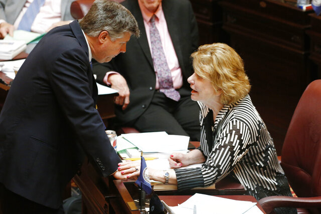 Virginia state Sen. Stephen Newman, R-Bedford, left, speaks with Senate Appropriations chairwoman, Sen. Janet Howell, after the Senate passed the budget bills during the Senate session at the Capitol Thursday March 12 , 2020, in Richmond, Va. (AP Photo/Steve Helber)