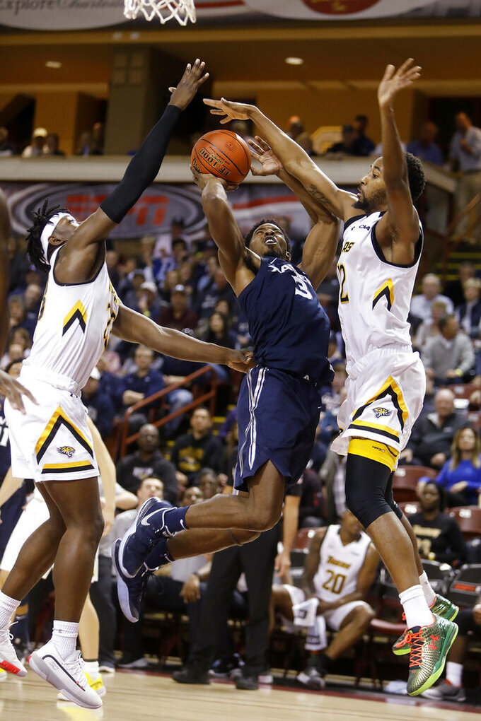 Xavier's Quentin Goodwin goes up for a shot between Towson's Brian Fobbs, left, and Juwan Gray during the first half of an NCAA college basketball game during the Charleston Classic on Thursday, Nov. 21, 2019, in Charleston, S.C. (AP Photo/Mic Smith)