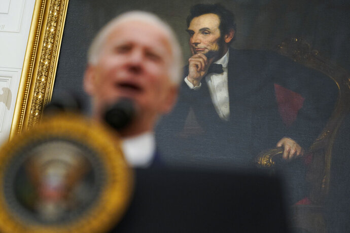 A portrait of former President Abraham Lincoln President hangs in the State Dining Room of the White House as Joe Biden delivers remarks on the economy Friday, Jan. 22, 2021, in Washington. (AP Photo/Evan Vucci)