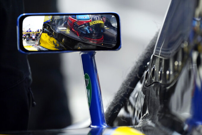 Colton Herta, reflected in a rearview mirror, sits in his car during practice for the Indianapolis 500 auto race at Indianapolis Motor Speedway, Thursday, May 20, 2021, in Indianapolis. (AP Photo/Darron Cummings)