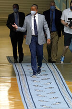 Hubert Davis enters the Dean E. Smith Center for a news conference at the University of North Carolina in Chapel Hill, N.C., Tuesday, April 6, 2021. Davis was named the Tar Heels' new NCAA men's basketball coach following the retirement of Roy Williams. (AP Photo/Gerry Broome)