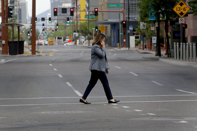 A lone pedestrian crosses a typically busy intersection in downtown Phoenix Wednesday, April 1, 2020 during the first full day of Arizona Gov. Doug Ducey's stay-at-home order to slow the spread of the new coronavirus. Gov. Ducey is urging Arizonans to be understanding and reasonable as people and businesses face April 1 due dates for bills such as mortgages, rent, utilities and internet service since the COVID-19 coronavirus outbreak has slowed the economy. The new coronavirus causes mild or moderate symptoms for most people, but for some, especially older adults and people with existing health problems, it can cause more severe illness or death. (AP Photo/Matt York)