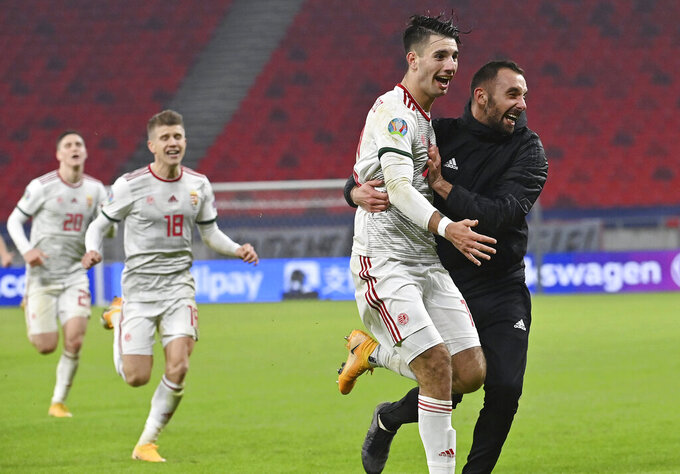Dominik Szoboszlai, second right, of Hungary celebrates with teammate Attila Fiola, right, after he scores his side's second, winning goal during the Euro 2020 playoff semifinal soccer match between Hungary and Iceland in Puskas Arena in Budapest, Hungary, Thursday, Nov. 12, 2020. (Tibor Illyes/MTI via AP)