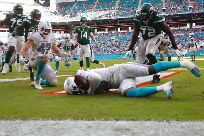 Miami Dolphins defensive end Taco Charlton, foreground, allows the ball to go out of the end zone in a safety during the second half of an NFL football game against the New York Jets, Sunday, Nov. 3, 2019, in Miami Gardens, Fla. (AP Photo/Wilfredo Lee)