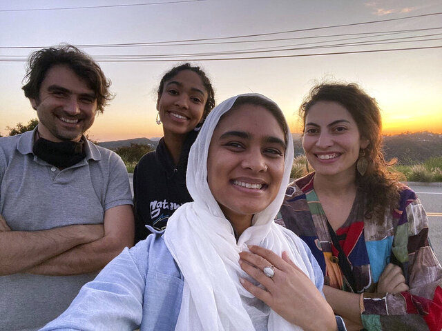 This undated photo provided by Ala' Khan shows Jonathan Simcosky, from left, Maya Mansour, Ala' Khan and Hadar Cohen, posing for a selfie while watching a sunset in celebration of the start of Ramadan in Los Angeles.   The four roommates moved into a five-bedroom, five-bath house in Los Angeles' Koreatown neighborhood earlier this year. They come from different faiths: Baha'i, Christianity, Islam and Judaism.   They live rent-free in a new interfaith experiment known as the Abrahamic House. (Photo courtesy of Ala' Khan via AP)