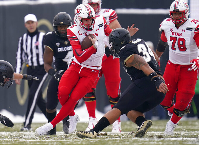 Utah quarterback Jake Bentley, front left, is pursued by Colorado linebacker Jamar Montgomery, back left, and defensive end Mustafa Johnson in the first half of an NCAA college football game Saturday, Dec. 12, 2020, in Boulder, Colo. (AP Photo/David Zalubowski)