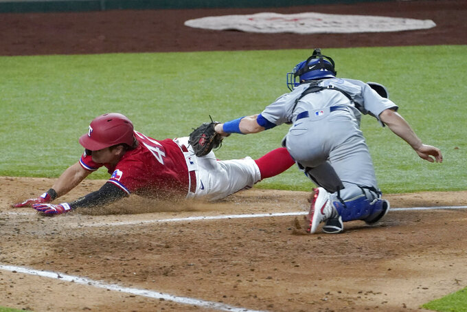 Texas Rangers' Shin-Soo Choo gets past the tag attempt by Los Angeles Dodgers catcher Will Smith to score on a sacrifice fly by Jose Trevino in the seventh inning of a baseball game in Arlington, Texas, Friday, Aug. 28, 2020. (AP Photo/Tony Gutierrez)