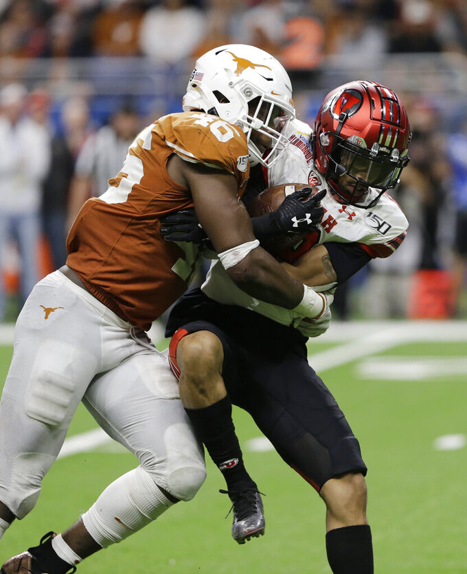 FILE - Texas linebacker Joseph Ossai (46) hits Utah wide receiver Derrick Vickers (8) during the second half of the Alamo Bowl NCAA college football game in San Antonio, Tuesday, Dec. 31, 2019. Ossai should have a big season in a new position. A linebacker in Texas' old 3-4 scheme, Ossai led Texas in tackles, then switched to a rush end position in the Alamo Bowl and delivered three sacks in a dominant win over Utah.(AP Photo/Austin Gay, File)