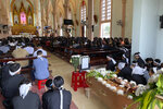 Relatives of Bui Thi Nhung sit next to her casket during a funeral ceremony inside Phu Thang church ahead of Nhung's burial on Sunday, Dec. 1, 2019 in the village of Do Thanh, Vietnam. The body of 19-year old Nhung was among the last remains of the 39 Vietnamese who died while being smuggled in a truck to England last month that were repatriated to their home country on Saturday. (AP Photo/Hau Dinh)