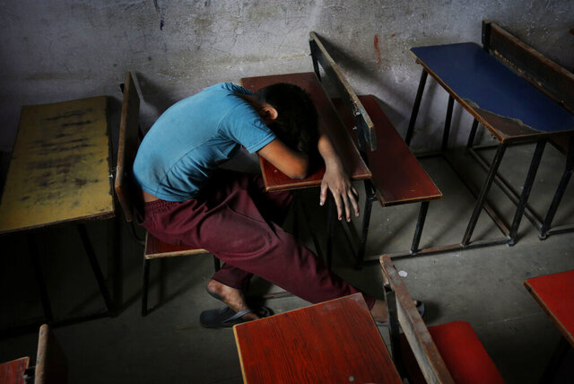 FILE - In this Tuesday, June 11, 2013, file photo, a bonded child laborer rests on a school desk in a safe house after being rescued during a raid by workers from Bachpan Bachao Andolan, or Save Childhood Movement, at a garments factory in New Delhi, India. With classrooms shuttered and parents losing their jobs, many children are working in farms, illegal factories, brick kilns and roadside stalls, reversing decades of progress to stop child labor. In rural India, a nationwide lockdown imposed in March, 2020, pushed millions of people into poverty, encouraging trafficking of children from villages into cities for cheap labor. (AP Photo/Kevin Frayer, File)