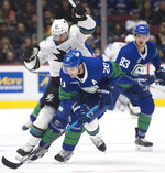 Vancouver Canucks center Brandon Sutter (20) fights for control of the puck with San Jose Sharks defenseman Erik Karlsson (65) during the second period of an NHL hockey game Saturday, Jan. 18, 2020, in Vancouver, British Columbia. (Jonathan Hayward/The Canadian Press via AP)