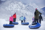 People drag their snow tubes for downhill sledding at the Frisco Adventure Park Thursday, March 7, 2019 in Frisco, Colo. Historic avalanche danger caused havoc in the Colorado mountains Thursday, shutting down portions of two highways and prompting a rare warning for drivers to avoid a route leading to some of the state's busiest ski resorts.(Hugh Carey/Summit Daily News via AP)