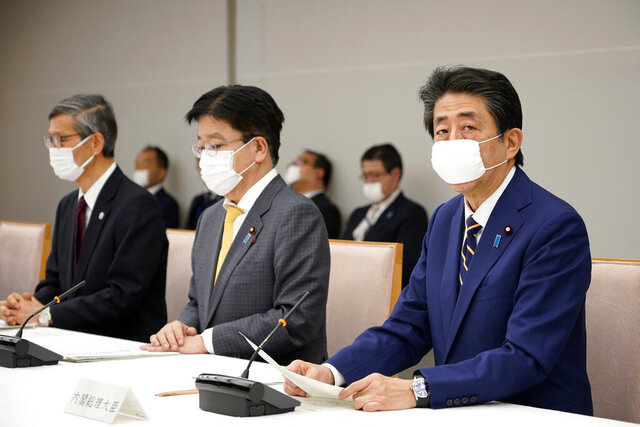 Japanese Prime Minister Shinzo Abe, right, declares a state of emergency during a meeting of the task force against the coronavirus at the his official residence in Tokyo, Tuesday, April 7, 2020. Abe declared a state of emergency for Tokyo and six other prefectures to ramp up defenses against the spread of the coronavirus. (Franck Robichon/Pool Photo via AP)