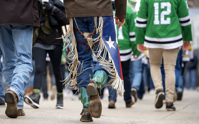 Ketch Weaver, of Buffalo, Texas, wears Texas themed chaps and cowboy boots as he walks into the Cotton Bowl before the NHL Winter Classic hockey game between the Dallas Stars and the Nashville Predators, Wednesday, Jan. 1, 2020, in Dallas. (AP Photo/Jeffrey McWhorter)