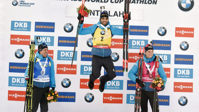 Second-placed Quentin Fillon Maillet, left, winner Martin Fourcade and third-placed Emilien Jacquelin, all of France, celebrate on the podium after the men's 12,5 km Pursuit competition, at the IBU Biathlon World Cup in Kontiolahti, Finland, Saturday March 14, 2020.  Fourcade retired from the sport on Saturday exactly ten years after his first World Cup victory in Kontiolahti. (Jussi Nukari/Lehtikuva via AP)