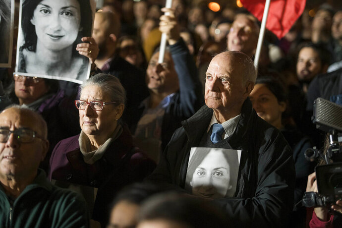 Rose and Michael Vella hold photos of their daughter, assassinated investigative journalist Daphne Caruana Galizia, as they partecipate in a demonstration in Valletta, Malta, Friday night, Nov. 29, 2019.  The family of the journalist who was killed by a car bomb in Malta is urging Maltese Prime Minister Joseph Muscat to resign, after his former chief aide was released from jail in a probe aimed at finding the mastermind of the 2017 murder. (AP Photo/Rene' Rossignaud)