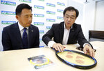 In this Nov. 5, 2018, photo, Wataru Hirokawa, right, executive office at Yonex's global marketing, and Nori Shimojo in charge of tennis player service at Yonex Co., show a racket similar to the model Japanese tennis player Naomi Osaka uses in her matches, at the company's headquarters in Tokyo. Osaka is headed for big money with both Japanese and global appeal after winning the U.S. Open. Tennis racket maker Yonex Co. is one of companies with deals with Osaka. (AP Photo/Yuri Kageyama)