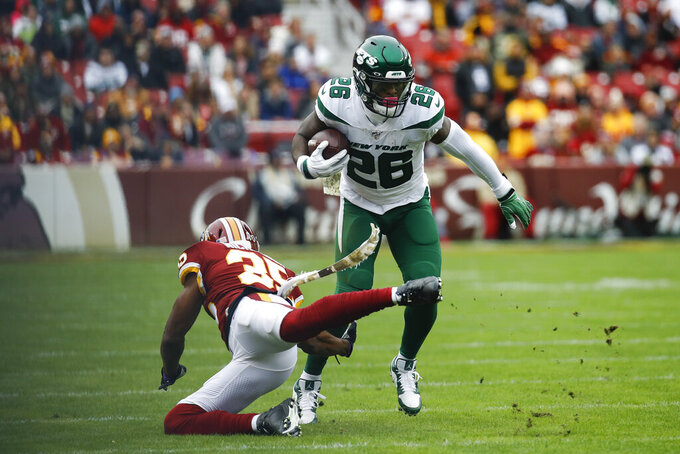 New York Jets running back Le'Veon Bell (26) moves past Washington Redskins strong safety Montae Nicholson (35) in the first half of an NFL football game, Sunday, Nov. 17, 2019, in Landover, Md. (AP Photo/Patrick Semansky)