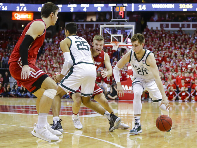 Michigan States's Matt McQuaid (20) drives against Wisconsin's Ethan Happ, left, and Brad Davison during the first half of an NCAA college basketball game Tuesday, Feb. 12, 2019, in Madison, Wis. (AP Photo/Andy Manis)