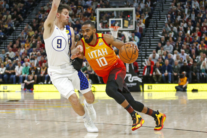 Utah Jazz guard Mike Conley (10) drives around Indiana Pacers guard T.J. McConnell (9) in the second half of an NBA basketball game Monday, Jan. 20, 2020, in Salt Lake City. (AP Photo/Rick Bowmer)