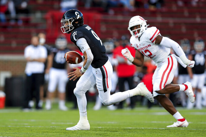 Cincinnati quarterback Desmond Ridder, left, carries the ball for a touchdown during the first half of an NCAA college football game against Houston, Saturday, Nov. 7, 2020, in Cincinnati. (AP Photo/Aaron Doster)