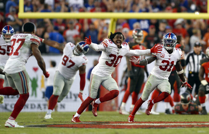 New York Giants players, including Antonio Hamilton (30), Sterling Shepard (87), Michael Thomas, and Dexter Lawrence (97) celebrate after the team defeated the Tampa Bay Buccaneers during an NFL football game Sunday, Sept. 22, 2019, in Tampa, Fla. (AP Photo/Jason Behnken)