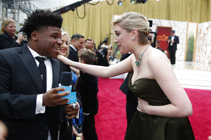 "FILE - In this Feb. 9, 2020 file photo, Greta Gerwig, right, talks to Jerry Harris on the red carpet at the Oscars at the Dolby Theatre in Los Angeles. Harris, the star of the Netflix documentary series ""Cheer,"" was arrested Thursday, Sept. 17 on child pornography charges. (AP Photo/John Locher File)"