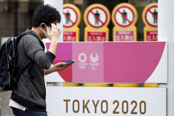 A man wearing a protective mask to help curb the spread of the coronavirus walks near an advertisement of Tokyo 2020 Olympic and Paralympic Games Tuesday, June 29, 2021, in Tokyo. (AP Photo/Eugene Hoshiko)