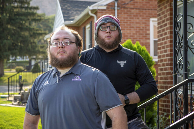 In this image provided by Weber State University, twin brothers Armand, left, and Antonio Berry, students at Weber State University, pose Aug. 20, 2020, in Ogden, Utah. The twin brothers were left legally blind after being shaken as babies by their biological father. This year, the university gave the Wildcat Achievement Award to Armand Berry to recognize his dedication to online learning made more challenging by his disability. His brother Antonio nominated him for the honor. (Benjamin Zack/Weber State University via AP)
