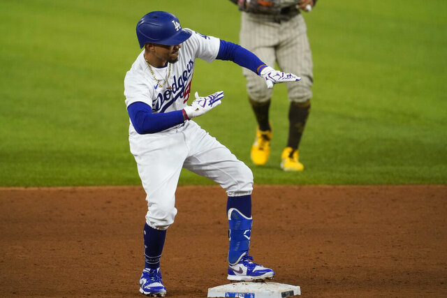 Los Angeles Dodgers right fielder Mookie Betts (50) celebrates after hitting a double against the San Diego Padres during the sixth inning in Game 1 of a baseball NL Division Series, Tuesday, Oct. 6, 2020, in Arlington, Texas. (AP Photo/Tony Gutierrez)