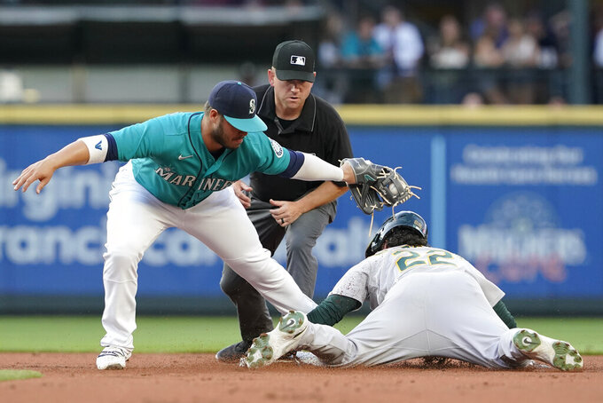 Oakland Athletics' Ramon Laureano, right, is caught stealing second base by Seattle Mariners second baseman Ty France, as umpire Mike Muchlinski watches during the second inning of a baseball game Friday, July 23, 2021, in Seattle. (AP Photo/Ted S. Warren)